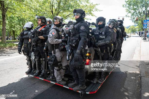 Police clad in riot gear wait to be called into action during the Patriot Prayer Rally and counterprotests led by Antifa The Proud Boys organized the...