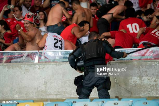 Police clash with Argentina's Independiente supporters after they won the championship in the 2017 Sudamericana Cup football final against Brazil's...