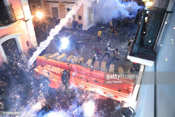 Police clash with protesters as they demonstrate against Ricardo Rossello the Governor of Puerto Rico near police that are manning a barricade set up...