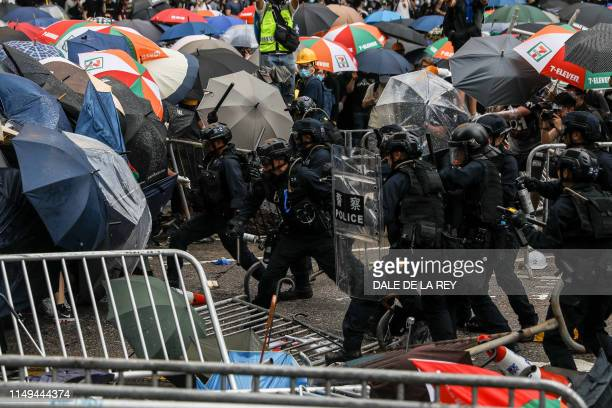 Police clash with protesters during a rally against a controversial extradition law proposal outside the government headquarters in Hong Kong on June...