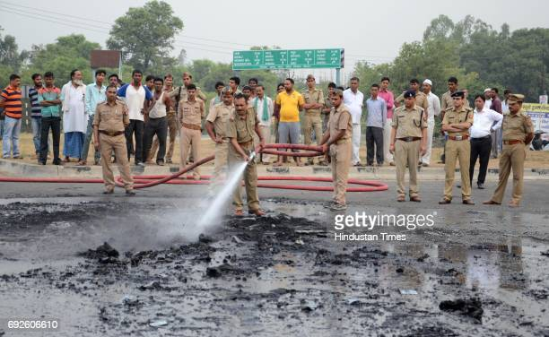 Police cleaning the spot where a bus was charred after the collision with truck near the Bareilly bypass on June 5 2017 in Bareilly India Twentytwo...