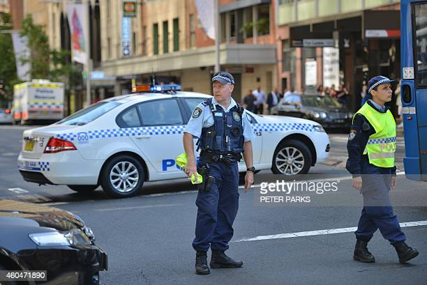 Police close a street where a cafe is being used to hold hostages in the central business district of Sydney on December 15 2014 Hostages were being...
