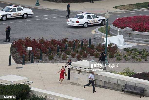 Police close in on the US Capitol as people run for cover after reports of a shooting October 3 2013 on Capitol Hill in Washington DC The US Capitol...