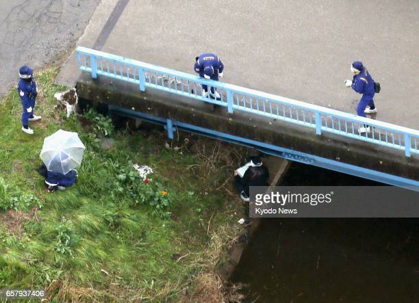 Police comb the area where the naked body of a girl was found March 26 2017 in a grass field near a drainage ditch in Abiko Chiba Prefecture The girl...