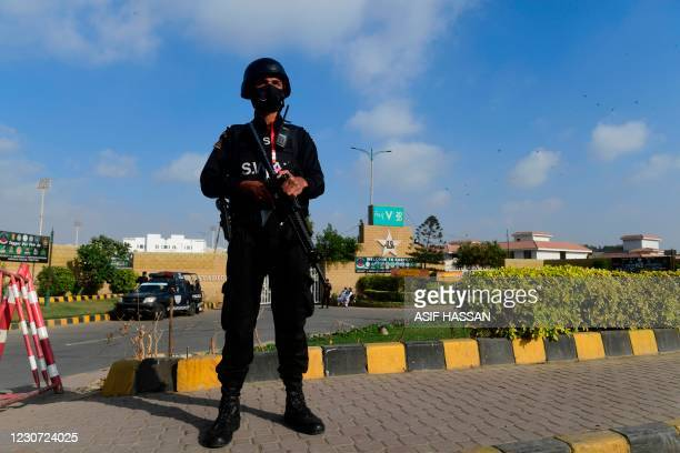 Police commando stands guard outside the National Stadiumas the Pakistan's cricket team attend a practice sessionin Karachi on January 22 ahead of...