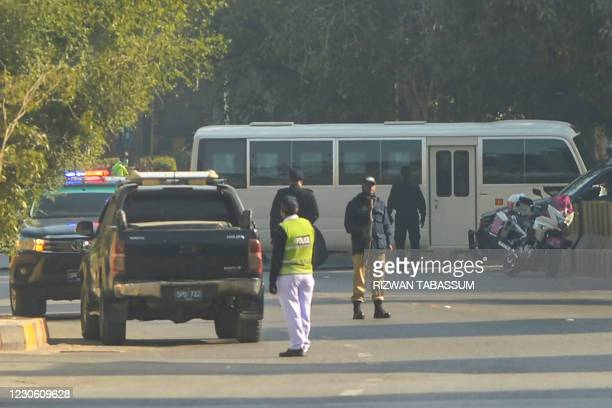 Police commandos stand guard as a bus transporting the South African cricket team enters a hotel in Karachi on January 16 upon their arrival to play...