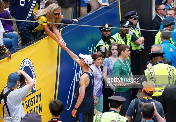 Police commissioner Bill Evans reaches up to shake hands with Mayor Walsh's girlfriend Lorrie Higgins after he crossed the finish line of the 121st...