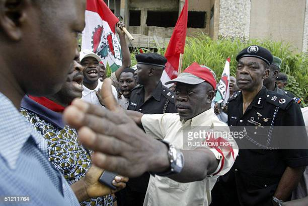 Police Commissioner Lawrence Alobi watches as President of the Nigeria Labour Congress Adams Oshiomhole directs protesting workers to return to its...