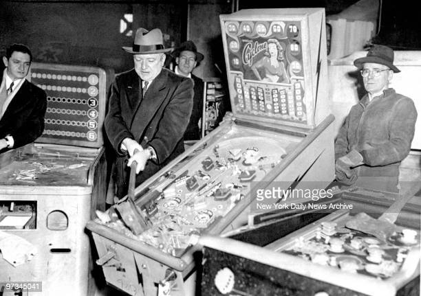 Police Commissioner William P O'Brien smashes illegal pinball machines in a warehouse in the Greenpoint section of Brooklyn
