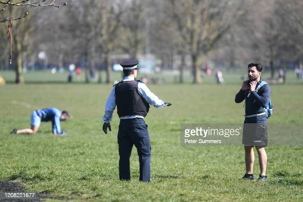 Police Community Support Officer is seen speaking to people exercising on Clapham Common on March 25, 2020 in London, England. British Prime...