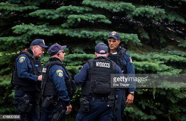 Police confer outside the Clinton Correctional Facility on June 12, 2015 in Dannemora, New York. Law enforcement continued their search for prisoners...