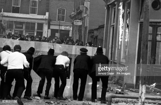 Police confront a group of youths from behind their riot shields in Mayall Road Brixton during renewed fighting between police and black youths