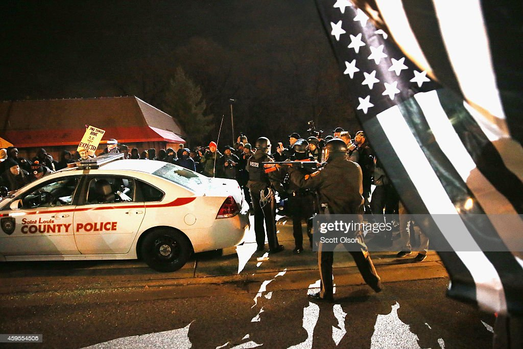 Police confront protestors after they attacked a squad car when riioting broke out following the grand jury announcement in the Michael Brown case on November 24, 2014 in Ferguson, Missouri. Ferguson has been struggling to return to normal after Brown, an 18-year-old black man, was killed by Darren Wilson, a white Ferguson police officer, on August 9. His death has sparked months of sometimes violent protests in Ferguson. A grand jury today declined to indict officer Wilson.