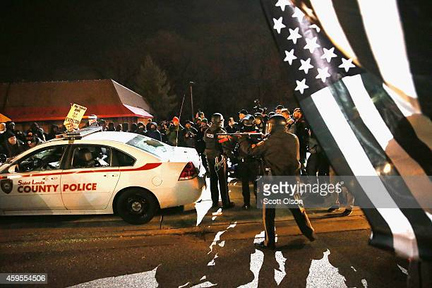 Police confront protestors after they attacked a squad car when riioting broke out following the grand jury announcement in the Michael Brown case on...