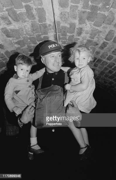 Police Constable Punter who is six foot seven inches tall carries two young children in to an underground air raid shelter under his command below a...