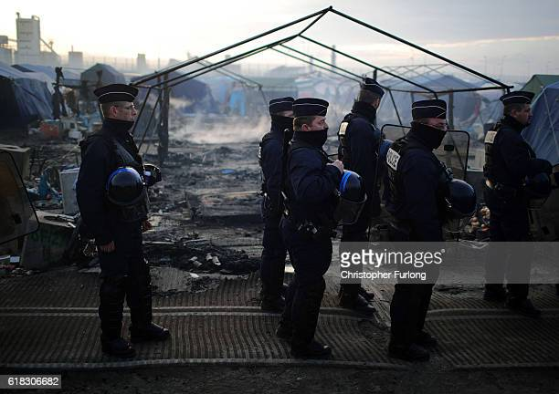 Police continue to check the huts and make shift homes for migrants in the Jungle camp as authorities demolish the site on October 26 2016 in Calais...