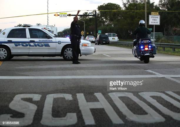 Police control a road near the Marjory Stoneman Douglas High School where 17 people were killed by a gunman yesterday on February 15 2018 in Parkland...