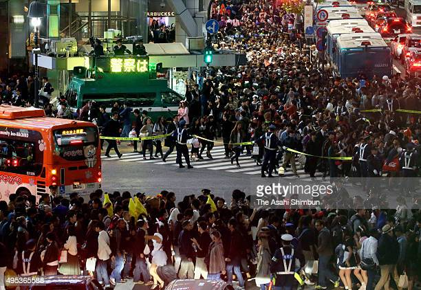 Police control the traffic at Shibuya crossing at Halloween night on October 31 2015 in Tokyo Japan