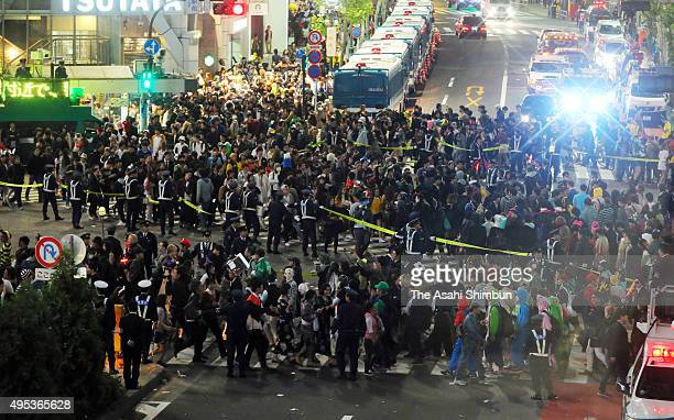 Police control the traffic at Shibuya crossing at Halloween night after midnight on November 1 2015 in Tokyo Japan
