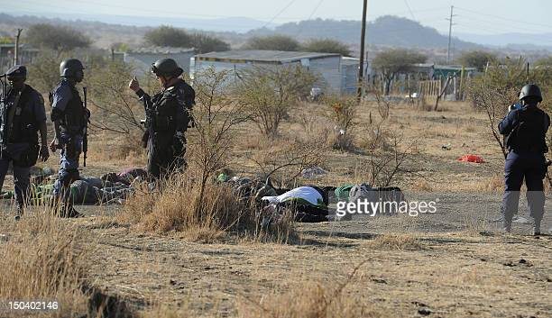 Police controls miners lying on the floor during an illegal strike at a mountain close to the mine near Rustenburg on August 16 2012 Police on...