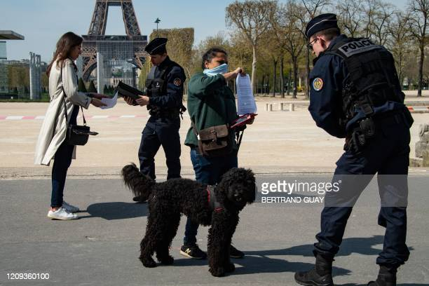 TOPSHOT Police controls passersby's papers near the Eiffel tower in Paris on April 7 during the 22nd day of a lockdown in France aimed at curbing the...
