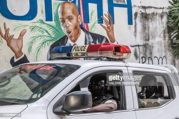 Police convoy drives past a wall painted with the president's image down the alley of the entrance to the residence of the president in...