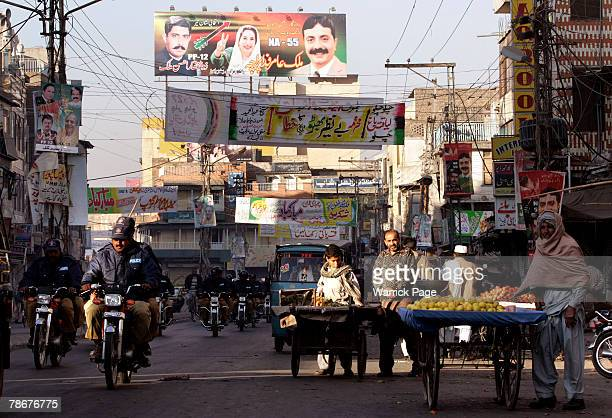 Police convoy rides past local traders selling their produce in spite of continued unrest in the wake of former prime minister, Benazir Bhutto's...