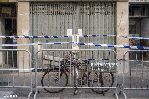 Police cordon tape runs through a bicycle in an area under lockdown in the Jordan area of Hong Kong, China, on Saturday, Jan. 23, 2021. Hong Kong is...