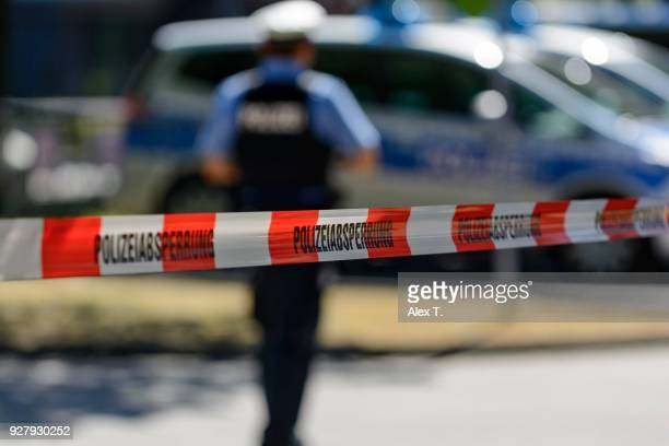 police cordon with barrier tape, at back patrol cars and police officers, frankfurt am main, germany - cordon boundary stock pictures, royalty-free photos & images