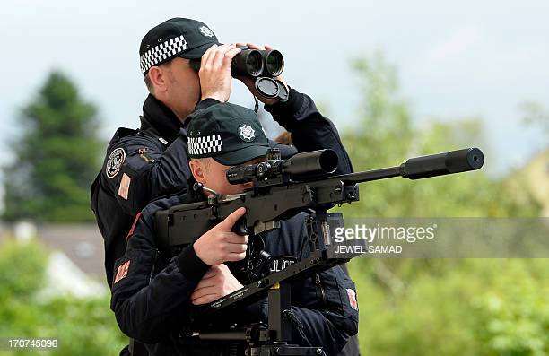 Police counter sniper armed units scan an area as US President Barack Obama and British Prime Minister David Cameron visit the Enniskillen Integrated...