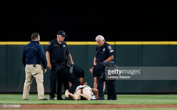 Police cover a streaker with a towel after tackling him in the ninth inning during the game against the Toronto Blue Jays and Seattle Mariners at...