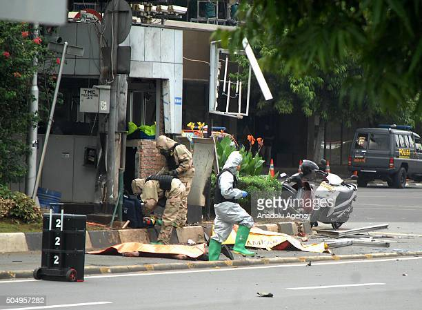 Police cover the bodies of civilian victims of terrorist bomb explosion at the traffic police station in Sarina Jakarta on January 14 2016 Indonesian...