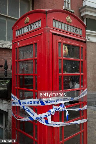 Police crime scene tape wrapped around a red phone box in Soho on 8th March 2017 London borough of Westminster England
