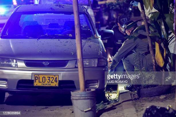 Police criminalistics technicians checked the area where an explosive device exploded in Aguablanca district in the east of Cali Colombia on August...
