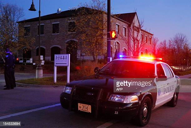A police cruiser and two officers stand guard outside the Azana spa in Brookfield Wisconsin where a gunman killed three people and shot four others...