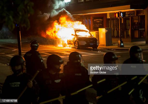A police cruiser burns behind the Police line near the intersection of Park and Tremont as a protest against police brutality pushes through the...