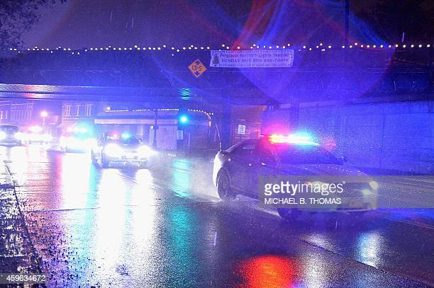 Police cruisers respond as demonstrators march in protest outside the Ferguson Police Department on November 26 2014 in Ferguson Missouri The streets...