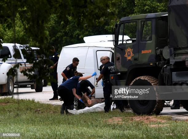 Police CSU investigators remove the body of one of the six members of the Saldivar family who died after crashing their van into Greens Bayou as they...