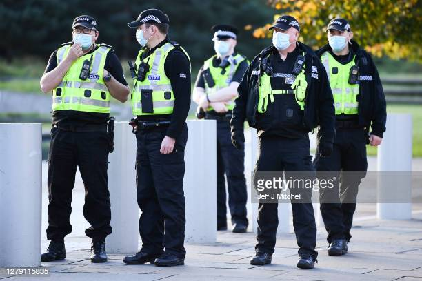 Police deal with protestors from Extinction Rebellion after they climbed on the roof of the Scottish Parliament where they have dropped a banner...