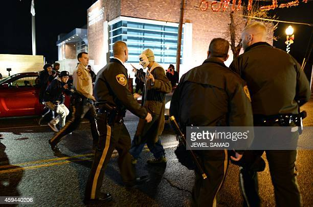 Police detain a demonstrator after he and others blocked a street near a police in Ferguson Missouri on November 23 2014 during a demonstration to...