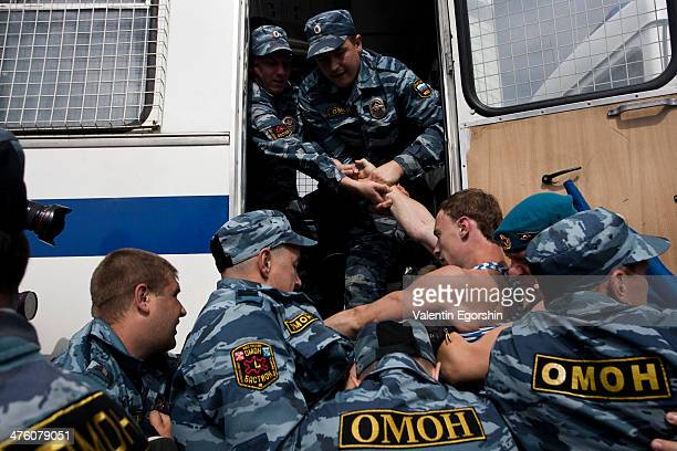 Police detain a former Russian paratrooper after he attacked a gay rights activist who was holding a one-man protest in St. Petersburg