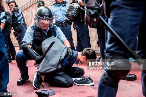 TOPSHOT Police detain a man after fights broke out inside a shopping mall between proChina supporters and antigovernment protesters in the Kowloon...