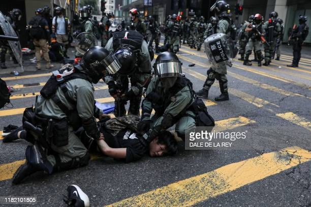 TOPSHOT Police detain a man during a flash mob to block roads in the Central district in Hong Kong on November 13 2019 Prodemocracy protesters...
