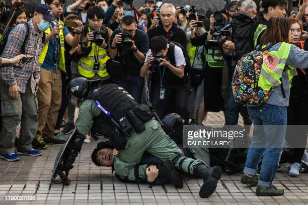 TOPSHOT Police detain a man during a rally in Hong Kong on December 22 2019 to show support for the Uighur minority in China Hong Kong riot police...