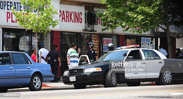 Police detain a man near the intersection of Florence and Western in Los Angeles on April 27, 2012 in California, ahead of the 20th anniversary of...