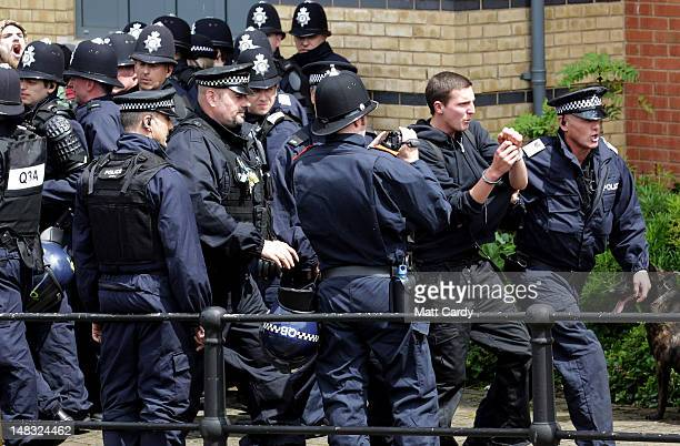 Police detain a man protesting against members of the English Defence League marching through Bristol on July 14 2012 in Bristol England A large...