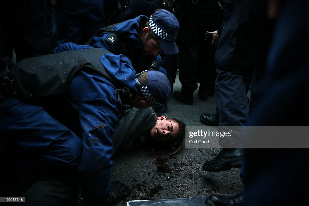 Police detain a protester after scuffles during a demonstration against fees and cuts in the education system on November 19, 2014 in London, England. A coalition of student groups have organised a day of nationwide protests in support of free education and to campaign against cuts. Photo by Carl Court/Getty Images)