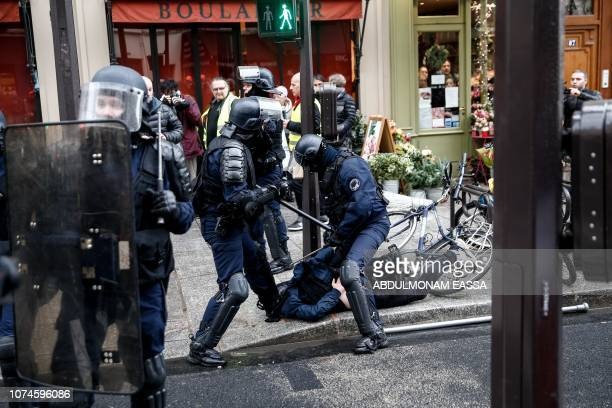 Police detain a protester during a 'Yellow Vest' antigovernment demonstration on December 22 in Paris as part of a nationwide day of demonstrations...