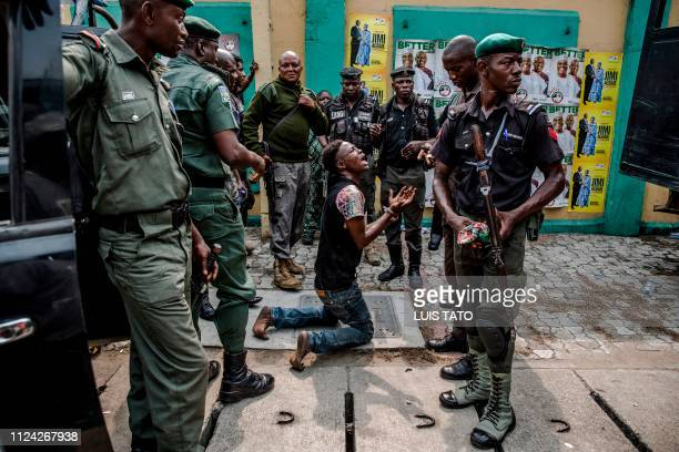 TOPSHOT Police detain an alleged thief in Lagos' Tafawa Balewa Square where the official People's Democratic Party opposition party is holding a...