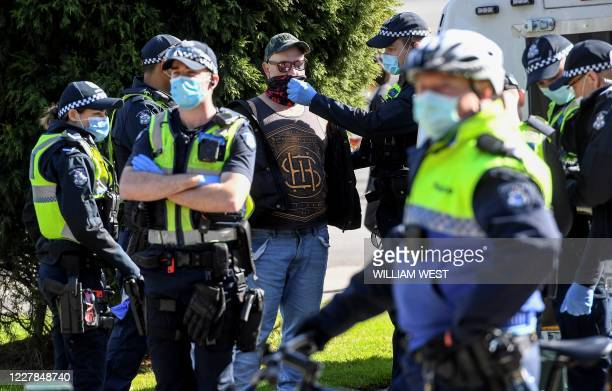 Police detain an anti-mask protester in Melbourne on July 31, 2020. - As greater Melbourne passed the halfway point of a lockdown initially intended...